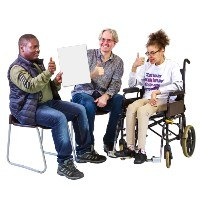 Three people looking at a paper. They are smiling and making the thumbs up sign