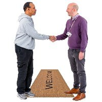 Two people shaking hands over a Welcome mat