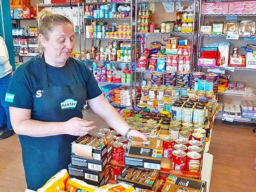 Volunteer working at ACE's Your Local Pantry shop
