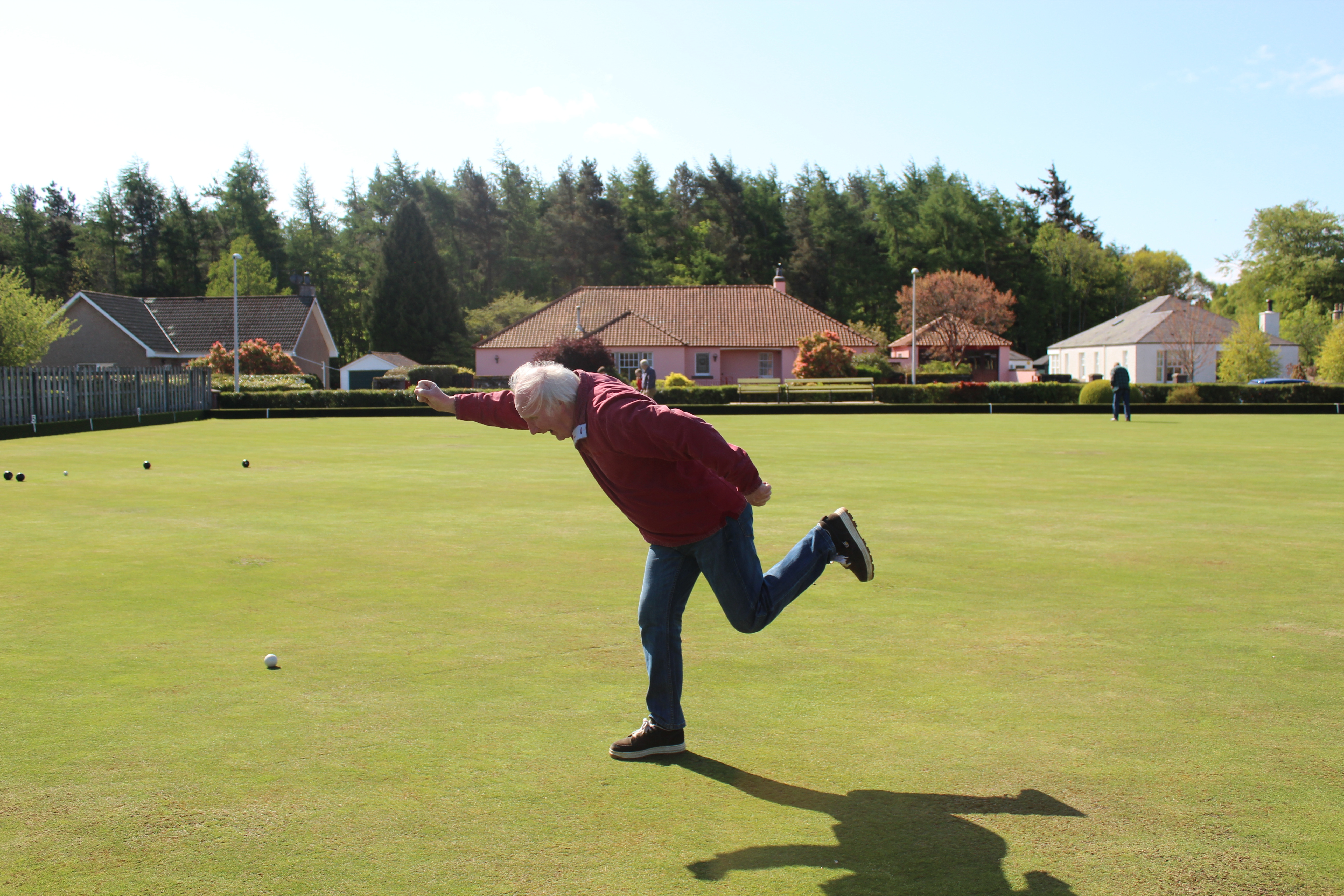An older man enthusiastically throws a ball on a picturesque bowling green.
