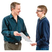 A man hands a paper to a second man. They are both smiling