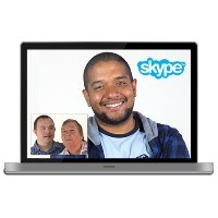 A computer screen showing people making a video call, with the Skype logo