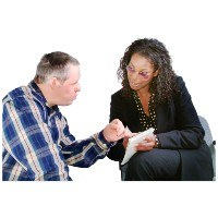 Woman and man looking at a paper together. He is pointing at the page, and she is speaking