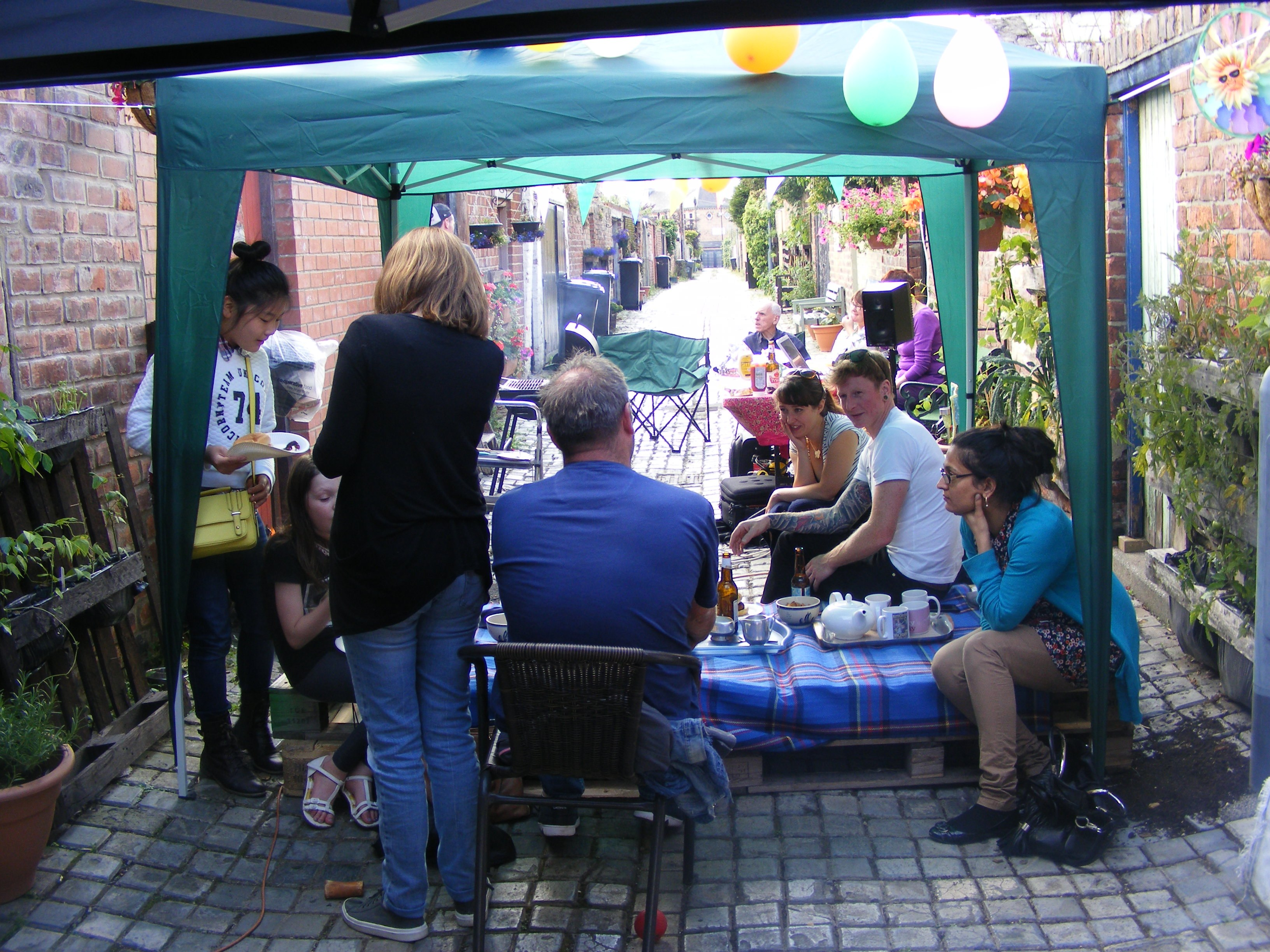 Members of Middlesbrough Environment City Alley Pals hosting an event in an alley behind terraced houses