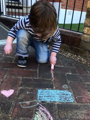 Young child chalking the pavement